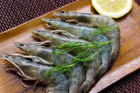 Fresh Shrimps with herbs and lemon on wooden plate Stock Photo