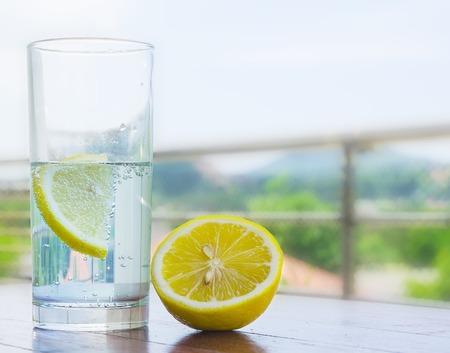 レモンは、白い背景で隔離の水のガラス