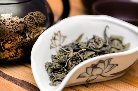 tea spoon: Dry green tea Da Hong Pao on wooden background
