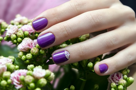 Woman hand with sparkle purple nail design and pink flower