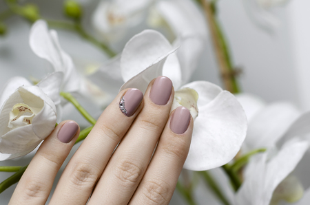 Beautiful female hand with beige nail design. Skin and nail care. 免版税图像