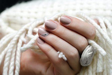 Beautiful female hand with warm beige nail design. Фото со стока