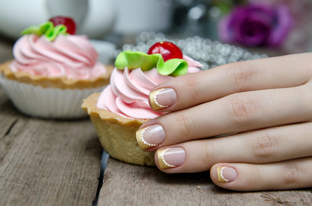 french manicure: Woman hand with gold french manicure hold sweet cupcake.