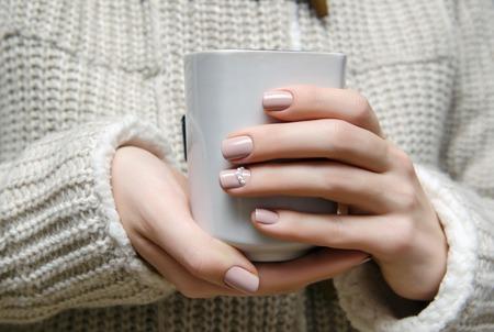温かみのあるベージュ ネイル デザイン holdinbg 白いカップと美しい女性の手。