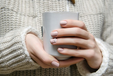 Beautiful female hand with warm beige nail design holdinbg a white cup. 免版税图像