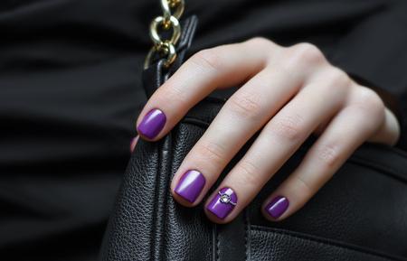 Frauenhand mit lila Nageldesign und schwarzen Handtasche.