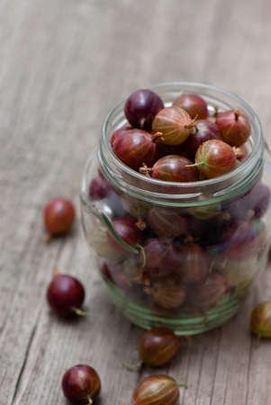 gooseberries: Gooseberries in glass jar on wooden table.