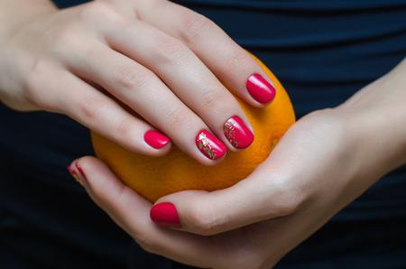 Female hand with dark pink nail design.