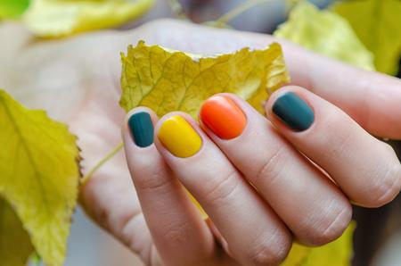 色のネイル デザインは、黄色を保持するいると女性の手の葉します。 写真素材