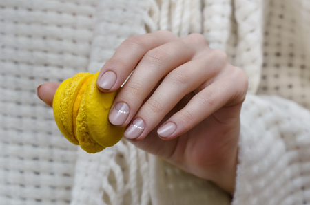 Female hand with natural beige nail design holding green macaroons