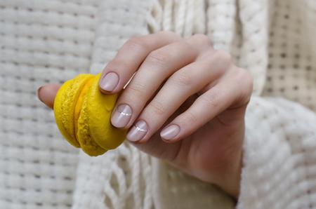 Weibliche Hand mit natürlichen beige Nageldesign hält grüne Makronen