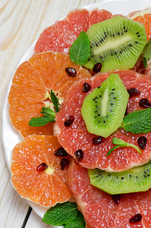 Healthy fresh fruit salad on white wooden background. Top view. Stock Photo