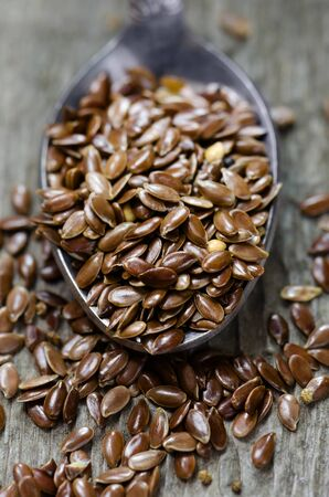 linseed: Flax seeds on a spoon. Wooden background.