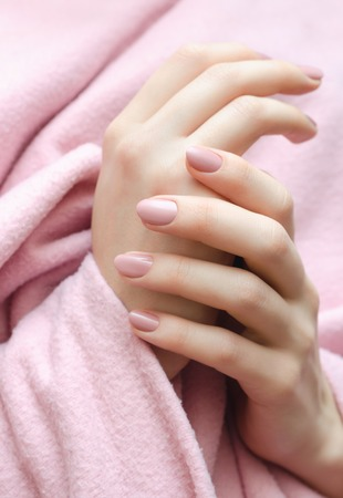 Beautiful female hand with warm pink manicure.