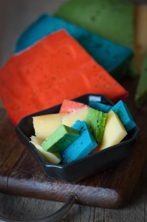 Cheese Mix. Gouda, blue, green and red cheese on wooden background.