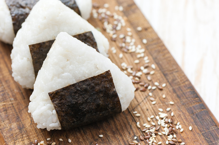 Onigiri. Rice triangle with nori seaweed on white plate.