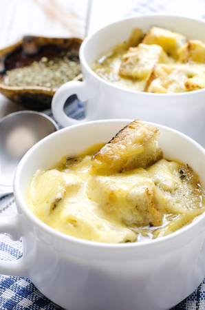 Onion soup with cheese in white bowl.