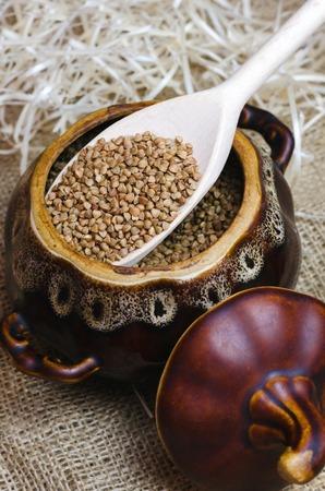 Raw buckwheat in a brown clay pot.