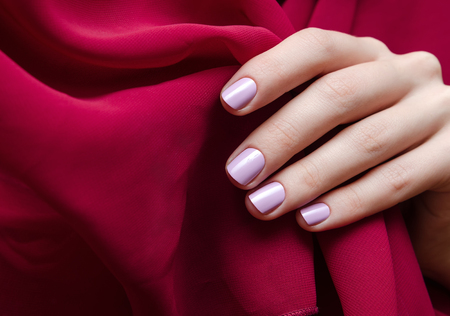 Beautiful female hand with light purple nail design holding red scarf.