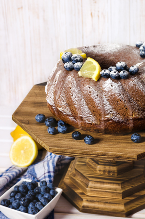 palate: Homemade lemon bundt cake with blueberries on wooden stand. Stock Photo