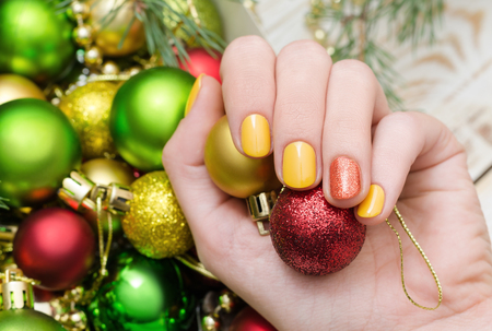 Beautiful female hand with yellow nail design. Christmas manicure with glitter accent. Stock Photo