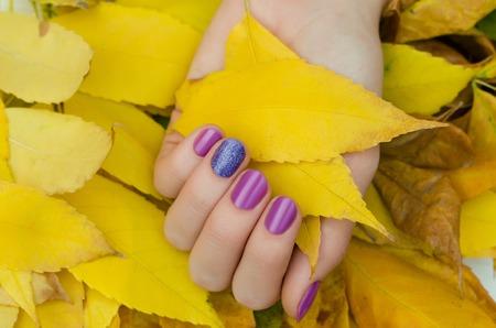 紫色のキラキラネイルデザインの女性の手。 写真素材
