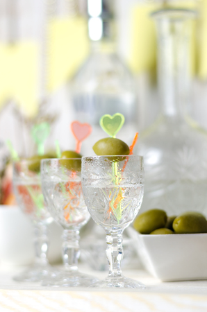 Vodka in the glass with olive. Drink bar, party.
