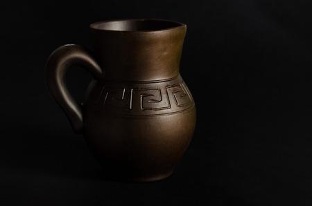 Clay jug, old ceramic vase on black background.