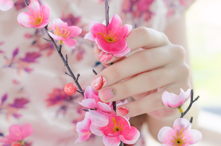 Female hands with pink nail design holding artificial cherry branch. Stock Photo