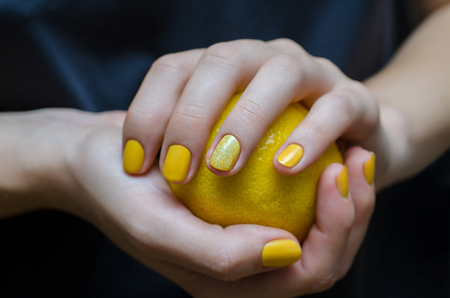 Female hands with yellow nail design holding lemon.
