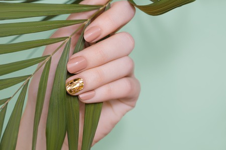 Beautiful female hand with beige nail design. Фото со стока