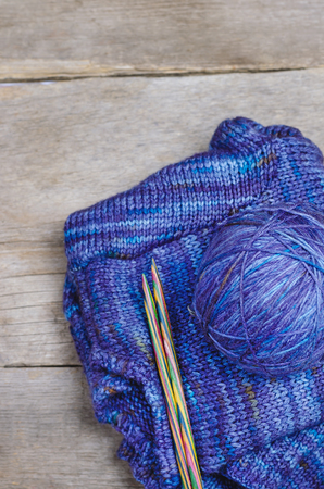 Threads for knitting on wooden background. Фото со стока