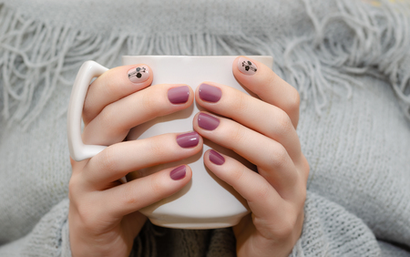 Female hands with dark pink nail design holding white cup.