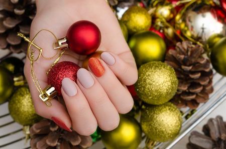 Schöne weibliche Hand mit Weihnachtsnageldesign. Standard-Bild