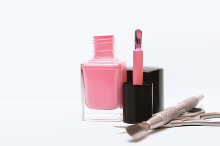 Bottle of pink nail polish and manicure tools on a table 写真素材
