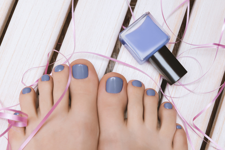 Beautiful female feet with blue pedicure on wooden background.