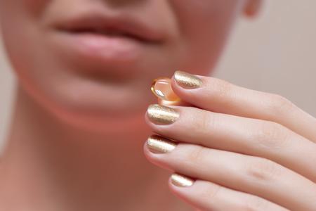 Woman holding omega 3 oil capsule, close up