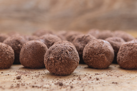 Chocolate candy and cocoa powder on wooden background.