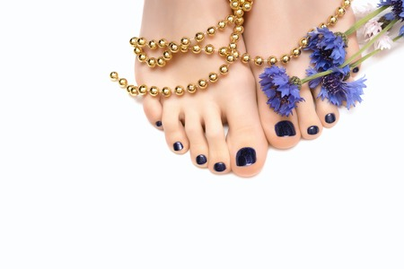 Female feet with blue pedicure and flower on white background.
