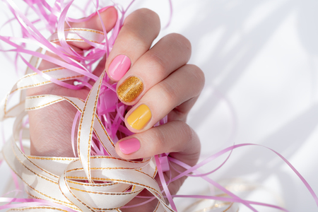 Female hand with yellow and pink nail design.