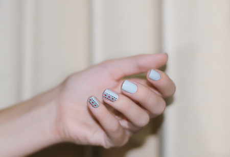 Female hand with light blue nail design.