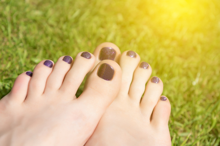 Female feet with purple pedicure on green grass.