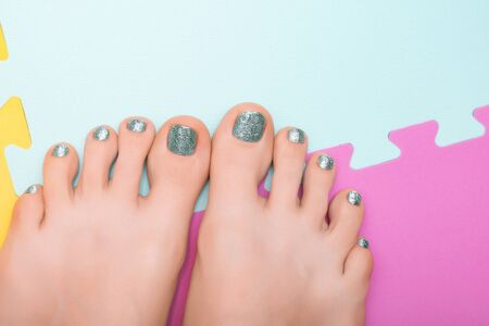 Beautiful female feet with blue glitter pedicure.