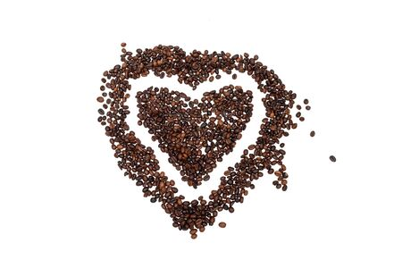 Coffee beans shaped as a heart on white background