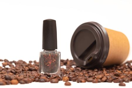 Nail polish bottle and coffee beans on white background