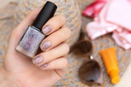 Female hands with glitter nail design holding nail polish bottle Banco de Imagens