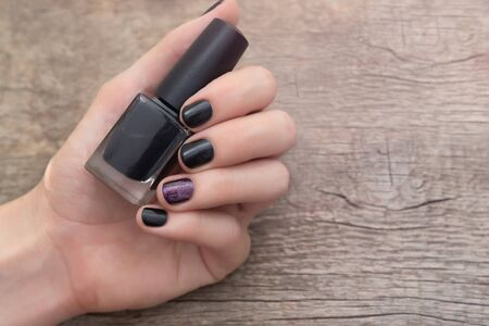 Female hand with purple nail design holding nail polish bottle
