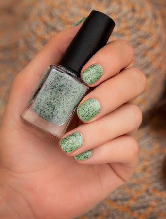 Female hand with green nail design holding nail polish bottle