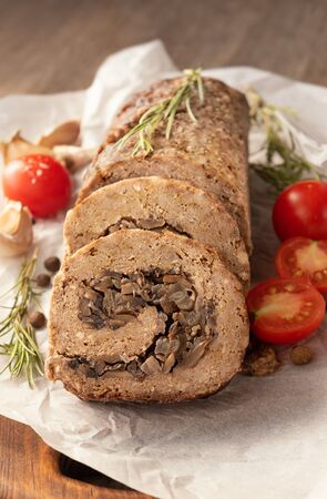 Tasty Meatloaf with mushrooms on wooden table Фото со стока