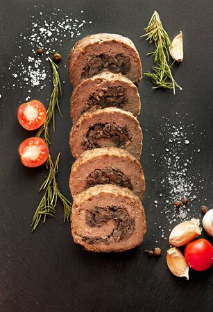 Tasty Meatloaf with mushrooms on black background Фото со стока